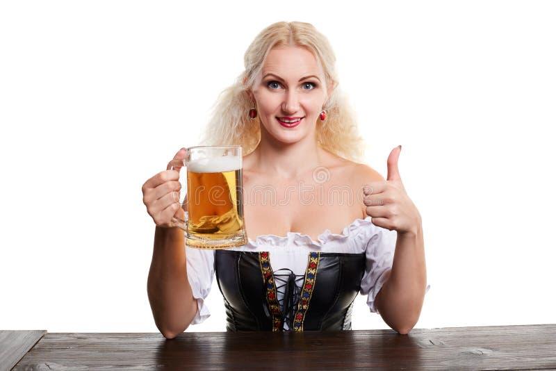 传统服装的美丽的年轻白肤金发的女孩喝在oktoberfest啤酒啤酒杯外面 免版税库存照片