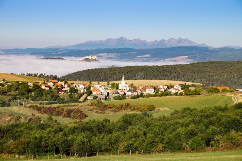传统村庄、城堡、草甸和山风景看法  免版税库存照片