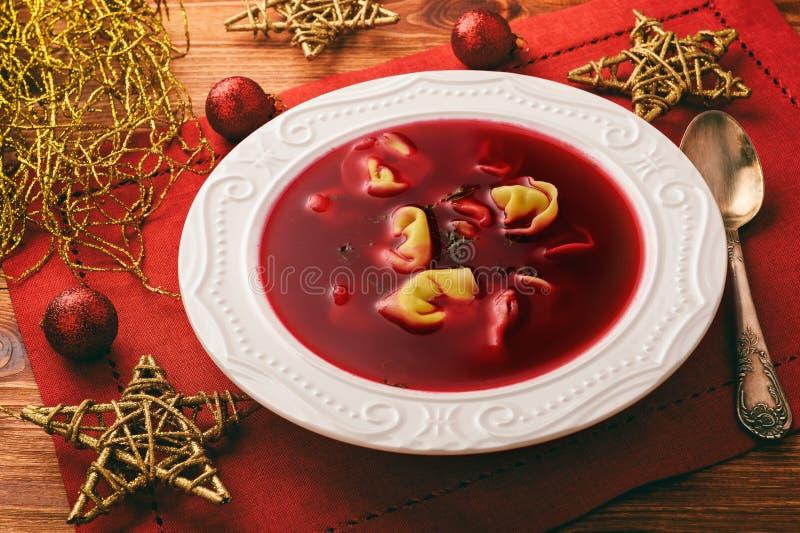 传统波兰圣诞节汤-红色罗宋汤汤用在白色板材的饺子 免版税库存图片