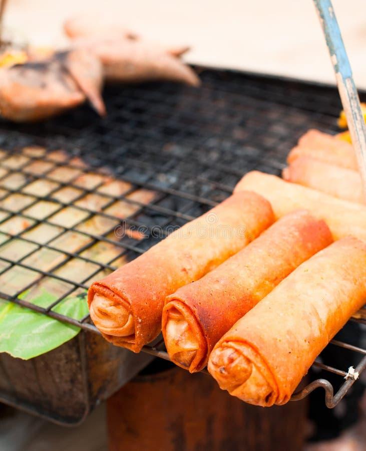 泰国食物在市场上。 在格栅的春卷 免版税图库摄影