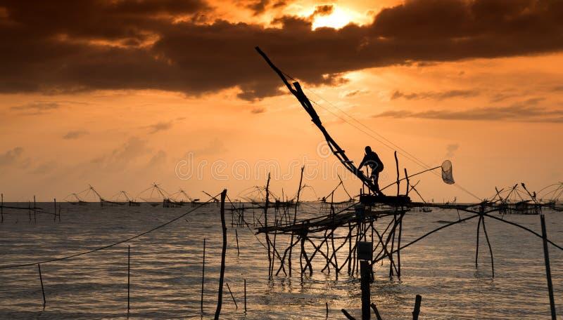 传统渔捞方法剪影使用一个竹方形的抄网的有日出天空背景 库存照片