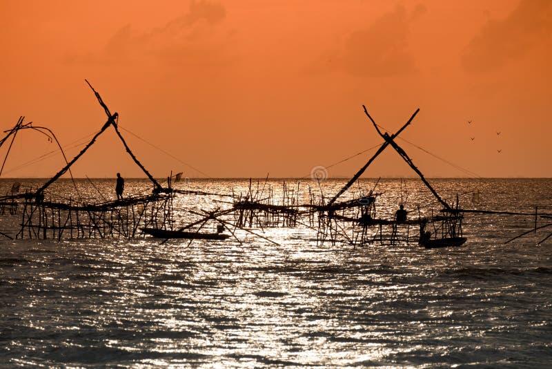 传统渔捞方法剪影使用一个竹方形的抄网的有日出天空背景 库存图片