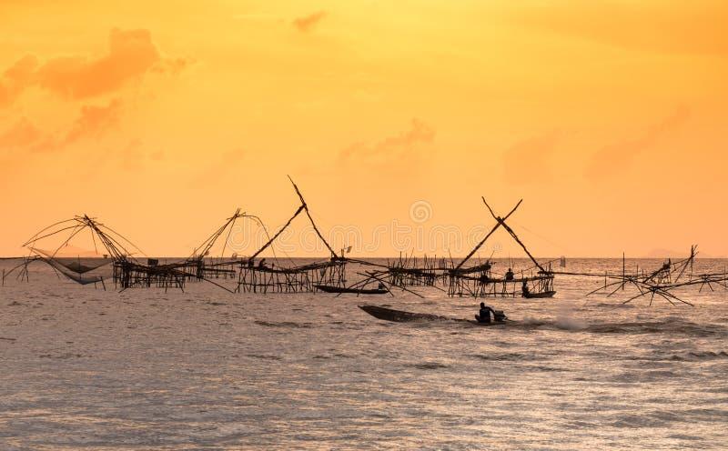 传统渔捞方法剪影使用一个竹方形的抄网的有日出天空背景 免版税库存图片