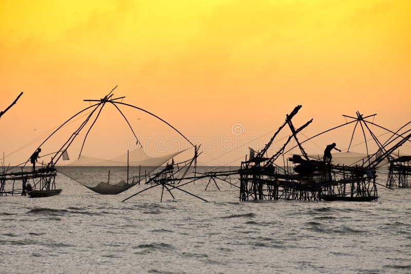 传统渔捞方法剪影使用一个竹方形的抄网的有日出天空背景 图库摄影