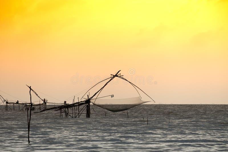 传统渔捞方法剪影使用一个竹方形的抄网的有日出天空背景 免版税库存照片