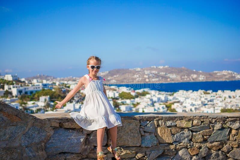 传统白色房子米科诺斯岛镇背景惊人的视图的可爱的小女孩  免版税库存照片