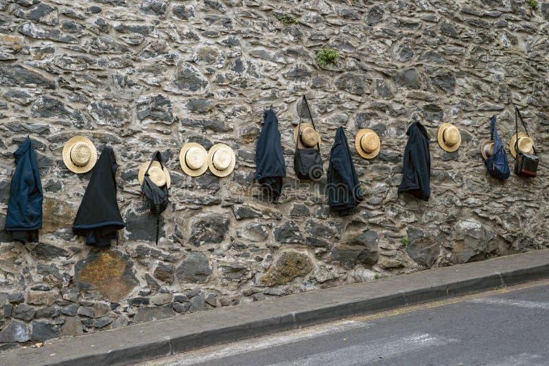 传统篮子爬犁车手,丰沙尔,马德拉岛海岛草帽和夹克  免版税库存照片