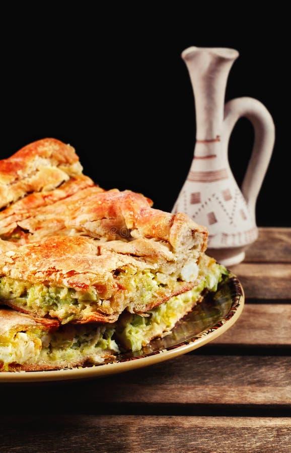 传统自创巴尔干韭葱和乳酪饼Zelnik服务与rakija 免版税库存照片