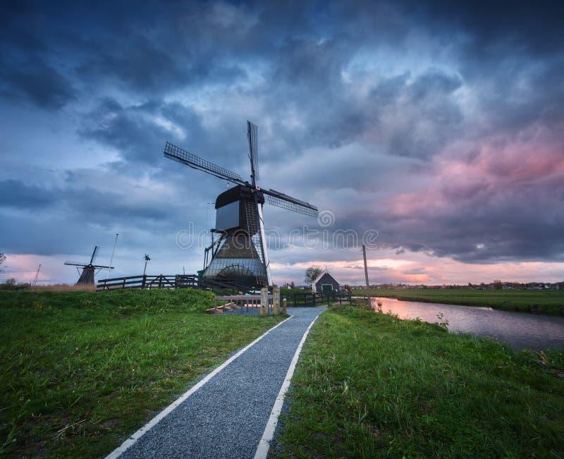 传统荷兰风车临近有多云天空的,风景水运河 免版税库存照片