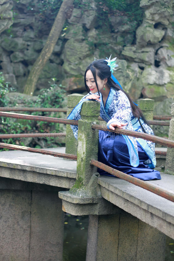 传统蓝色和白色Hanfu礼服的,在著名庭院攀登的戏剧亚裔中国妇女在弯的桥梁 免版税库存图片