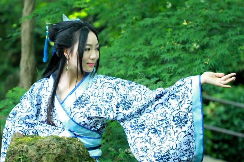 传统蓝色和白色Hanfu礼服的,戏剧亚裔中国妇女在一个著名庭院里 库存图片