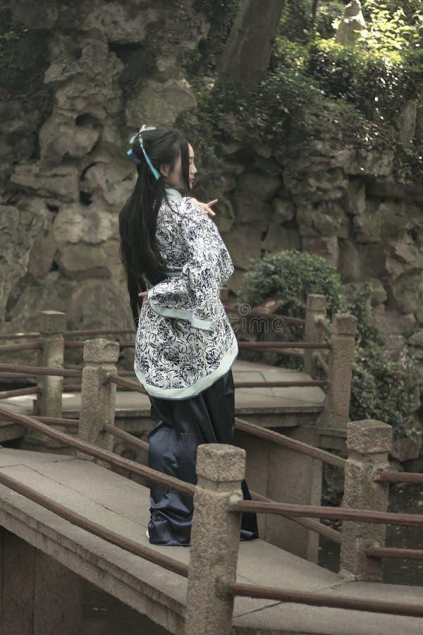 传统蓝色和白色Hanfu礼服的,戏剧亚裔中国妇女在弯曲的桥梁的一个著名庭院里 免版税图库摄影