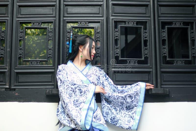 传统蓝色和白色Hanfu礼服的,戏剧亚裔中国妇女在窗口附近的一个著名庭院里 免版税库存照片