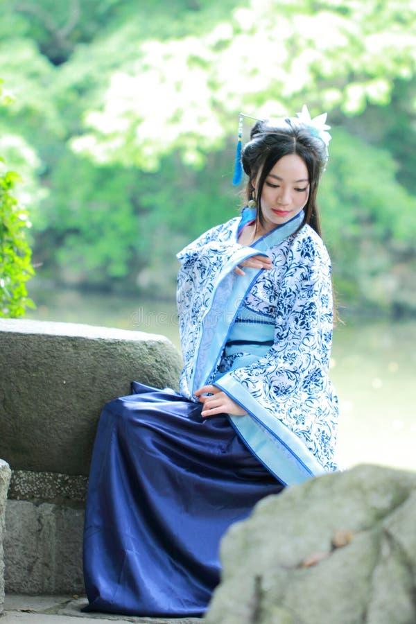 传统蓝色和白色Hanfu礼服的,杀害时间Aisan中国妇女在一个著名庭院里 免版税图库摄影