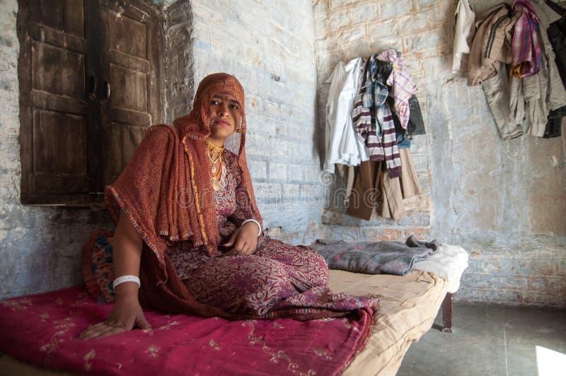 传统衣物和金首饰的印地安村庄妇女在房子里 村庄在乔德普尔城附近的塔尔沙漠 免版税库存图片