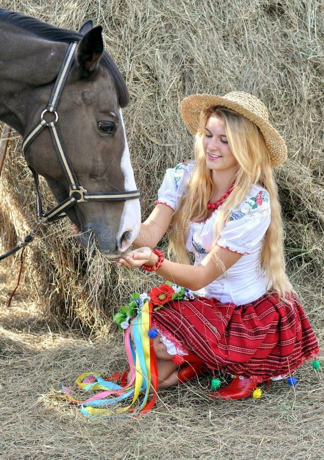 传统衣裳的乌克兰十几岁的女孩喂养马 免版税库存图片