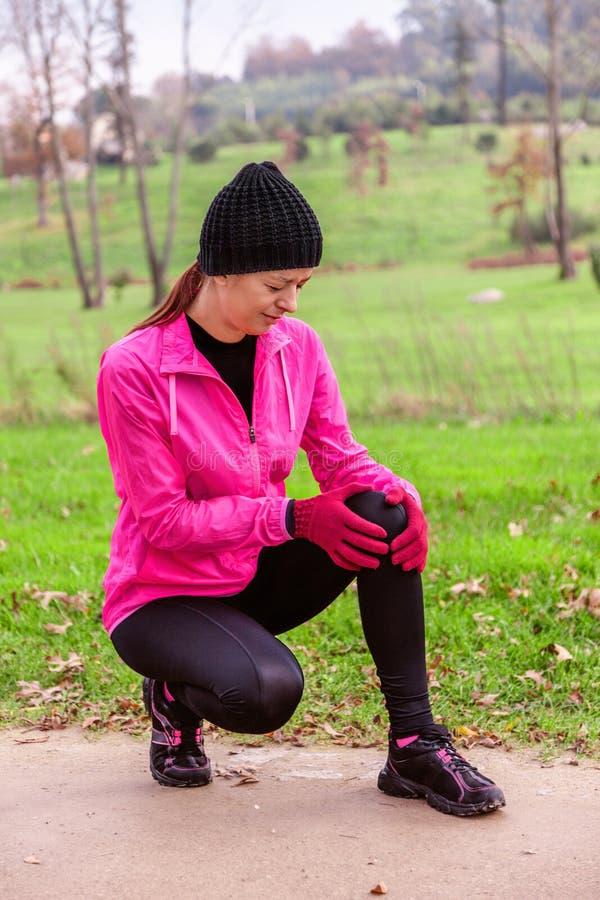 伤害从膝伤的女运动员在都市公园的训练轨道的一个冷的冬日 免版税库存图片