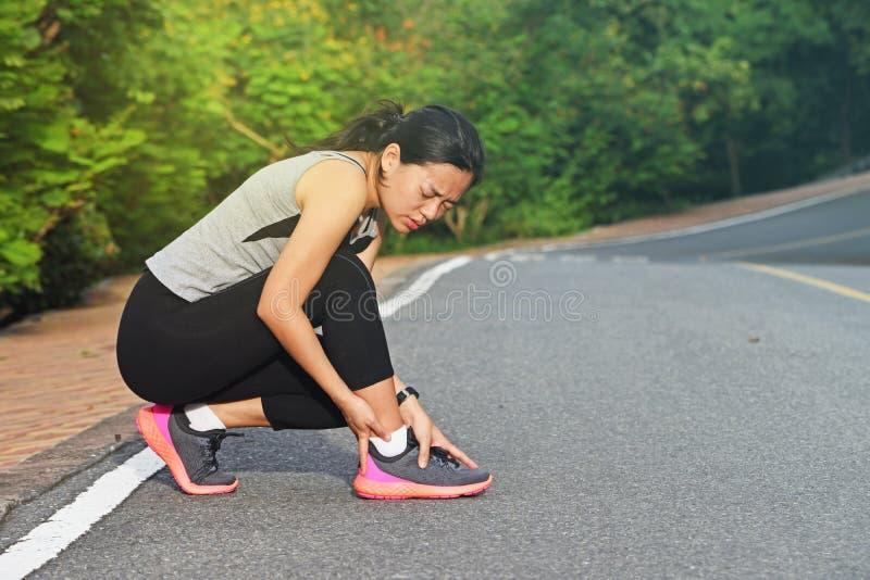 伤害妇女的赛跑者握痛苦的被扭伤的脚腕 免版税库存图片