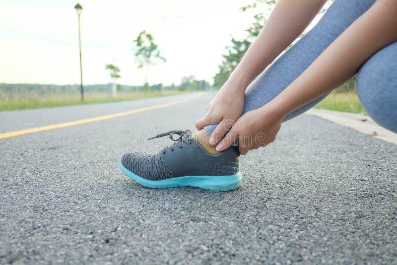 伤害连续伤害腿事故体育妇女的赛跑者在痛苦中握痛苦的被扭伤的脚腕 库存图片