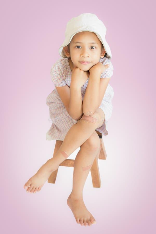 伤害逗人喜爱的女孩坐木位子 库存照片