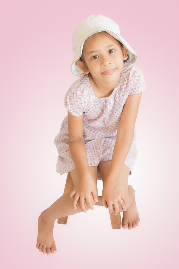 伤害逗人喜爱的女孩坐木位子 库存图片