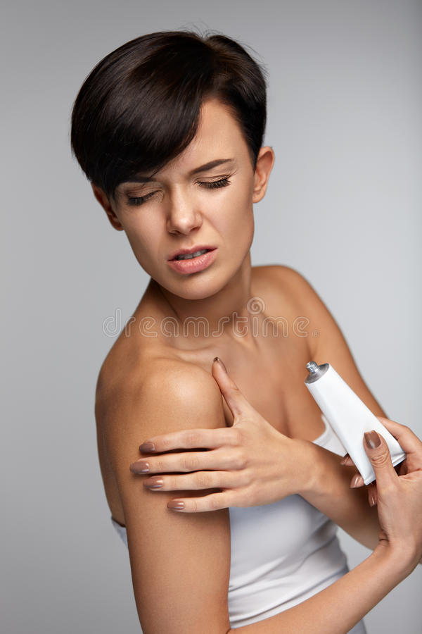 伤害治疗 充满胳膊痛苦的美丽的妇女,应用奶油 免版税图库摄影