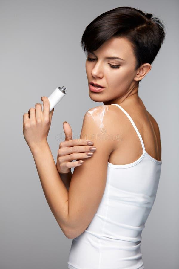伤害治疗 美好的妇女感觉痛苦,应用奶油 免版税库存图片