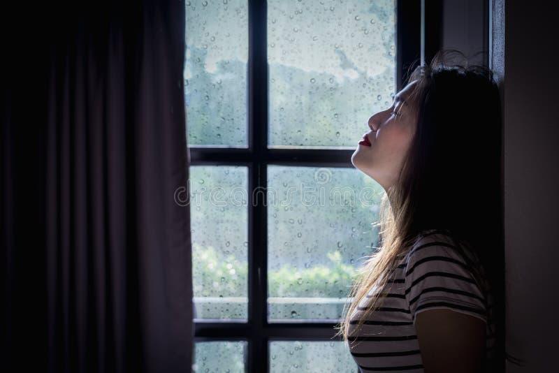 伤心妇女在一个暗室哭泣有雨季背景 库存照片