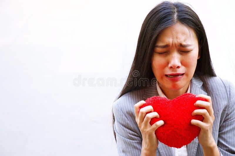 伤心妇女拿着与哀伤的表情的红色心脏 免版税库存照片