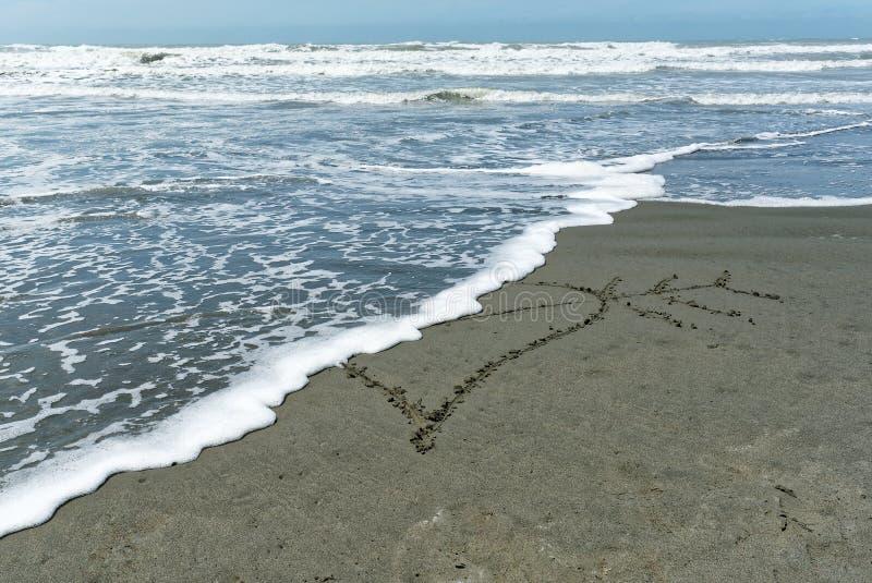 伤心,在沙子画的心脏切成两半被接踵而来的波浪 免版税库存照片