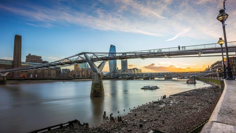 伦敦、英国-在千年桥梁的美好的日落有泰晤士河的和摩天大楼 库存图片