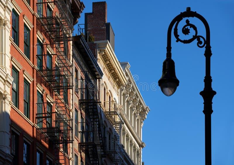 伦敦苏豪区与檐口、防火梯和路灯柱曼哈顿,纽约的大厦门面 免版税库存照片