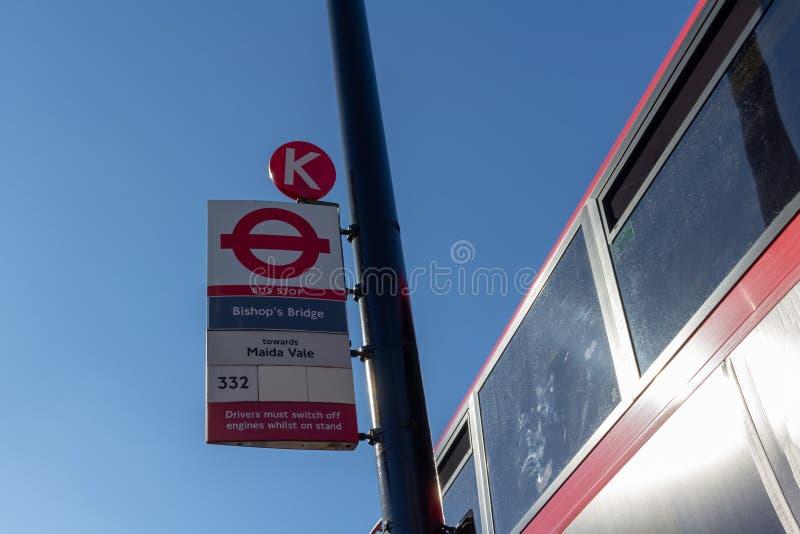 伦敦,英国–2018年10月21日:伦敦公交车站标志和公共汽车在背景,伦敦,英国 晴朗蓝色日的天空 库存照片