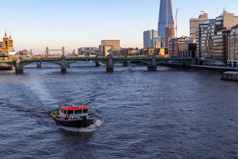 伦敦,英国–2018年12月13日:小船切口通过在一个蓝色海湾泰晤士河伦敦的水 库存图片