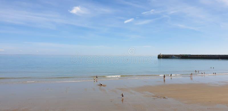 伦敦,英国,福克斯通,肯特:2019年6月1日:晴朗的沙子的游人使享用美丽的阳光和天空蔚蓝靠岸在 免版税库存图片