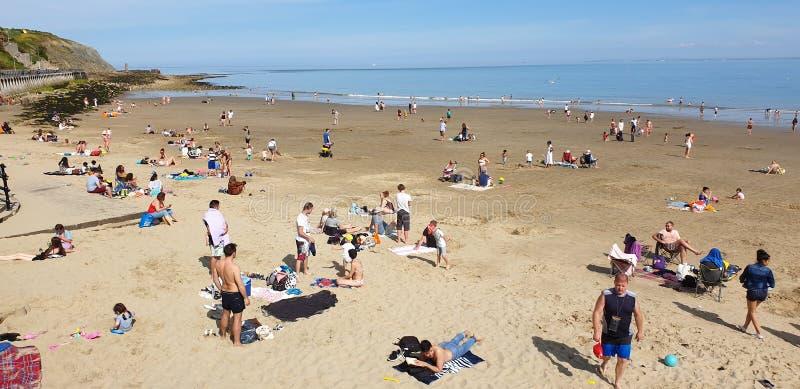 伦敦,英国,福克斯通,肯特:2019年6月1日:晴朗的沙子的游人使享用美丽的阳光和天空蔚蓝靠岸在 免版税图库摄影