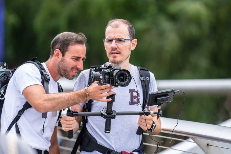 伦敦,英国,2019年7月 拍摄录影的两videographers在圣保罗座堂和千禧桥附近在泰晤士河  库存图片