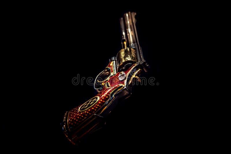 伦敦,英国,2018年12月10日:在黑背景隔绝的手枪左轮手枪 被修宝石的左轮手枪,定做了 357有红色的大酒瓶 库存图片