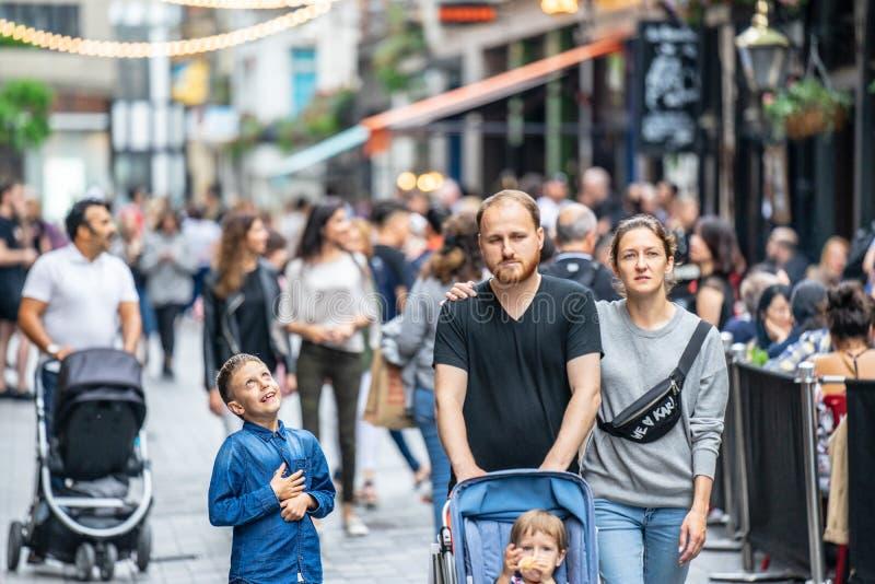 伦敦,英国,2019年7月28日 享受平衡的步行的愉快的英国家庭在Carnaby街在苏豪区 图库摄影