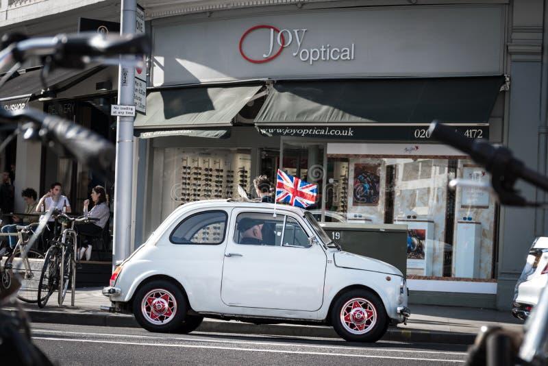 伦敦,英国-与英国旗子的小菲亚特在屋顶通过伦敦街道驾驶 图库摄影
