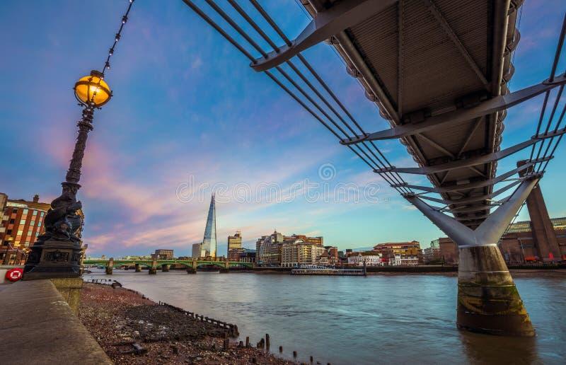 伦敦,英国-在千年桥梁的美好的日落场面有著名摩天大楼的 免版税库存图片