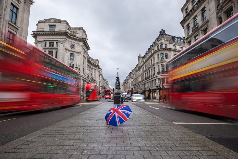 伦敦,英国-在繁忙的摄政的街道的英国伞有偶象红色双层汽车的 库存照片