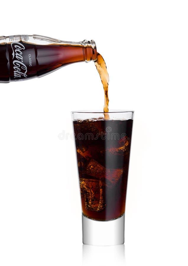 伦敦,英国- 2018年1月02日:倾吐的可口可乐苏打从瓶喝到在白色的玻璃 饮料导致并且被制造 库存照片