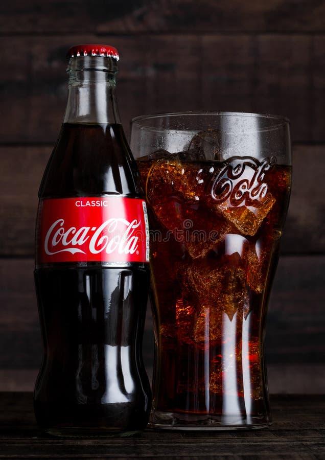 伦敦,英国- 2018年2月14日:原始的玻璃和瓶可口可乐喝与在木头的冰 饮料导致和manufact 图库摄影