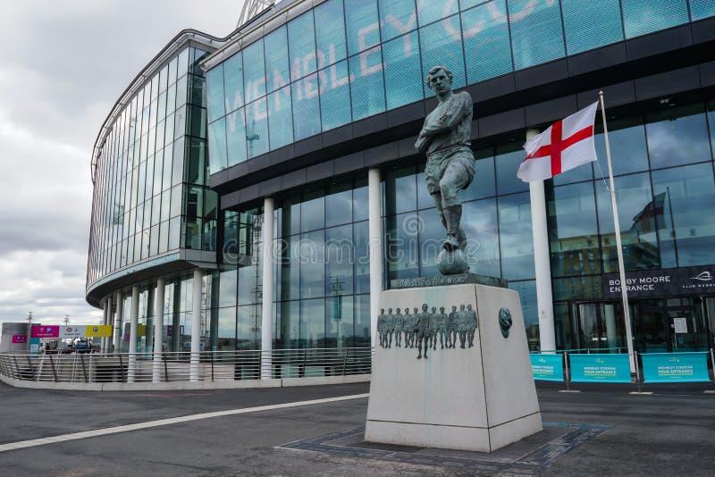 伦敦,英国- 2018年3月8日:在温布利球场前面的博比・摩尔的雕象在一个非常大风天 库存照片