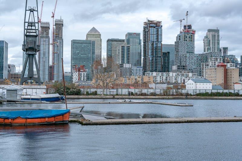 伦敦,英国- 2019年3月05日:在船坞停泊的大小船,当金丝雀塔和舱内甲板俯视的河沿公寓  免版税库存照片