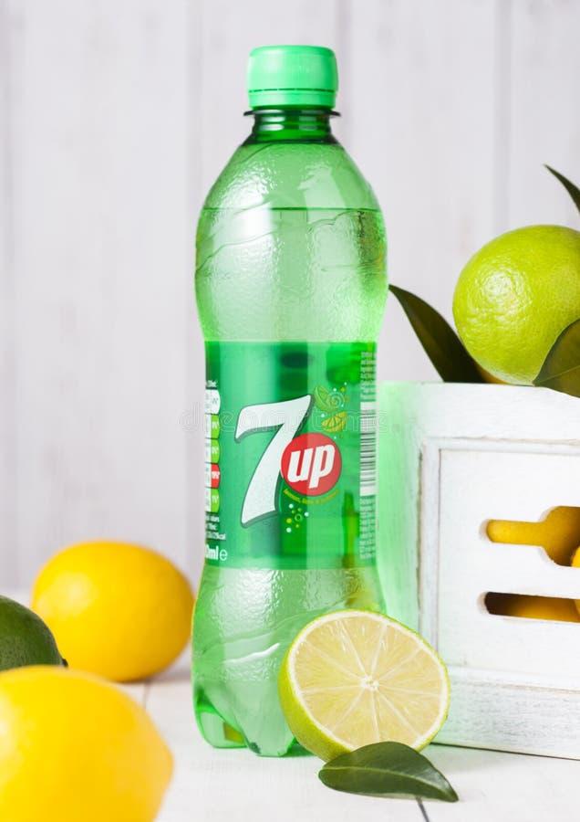 伦敦,英国- 2018年4月27日:塑料瓶7UP柠檬水苏打饮料用新鲜的柠檬和石灰在木背景 免版税库存照片