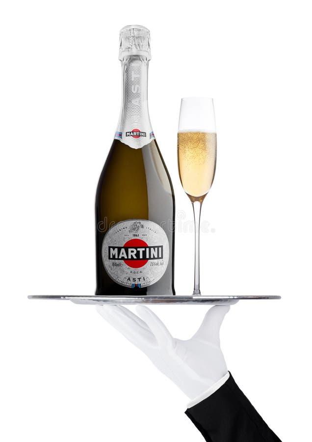 伦敦,英国- 2017年11月24日:有手套的手拿着有马蒂尼鸡尾酒阿斯蒂香槟瓶和玻璃的盘子 免版税库存图片