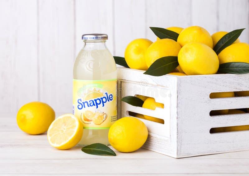 伦敦,英国- 2018年9月03日:瓶Snapple在木背景的柠檬汁用在木箱的新鲜的柠檬 Snapple是a 免版税库存图片