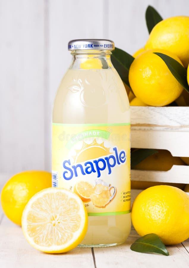 伦敦,英国- 2018年9月03日:瓶Snapple在木背景的柠檬汁用在木箱的新鲜的柠檬 Snapple是a 库存图片
